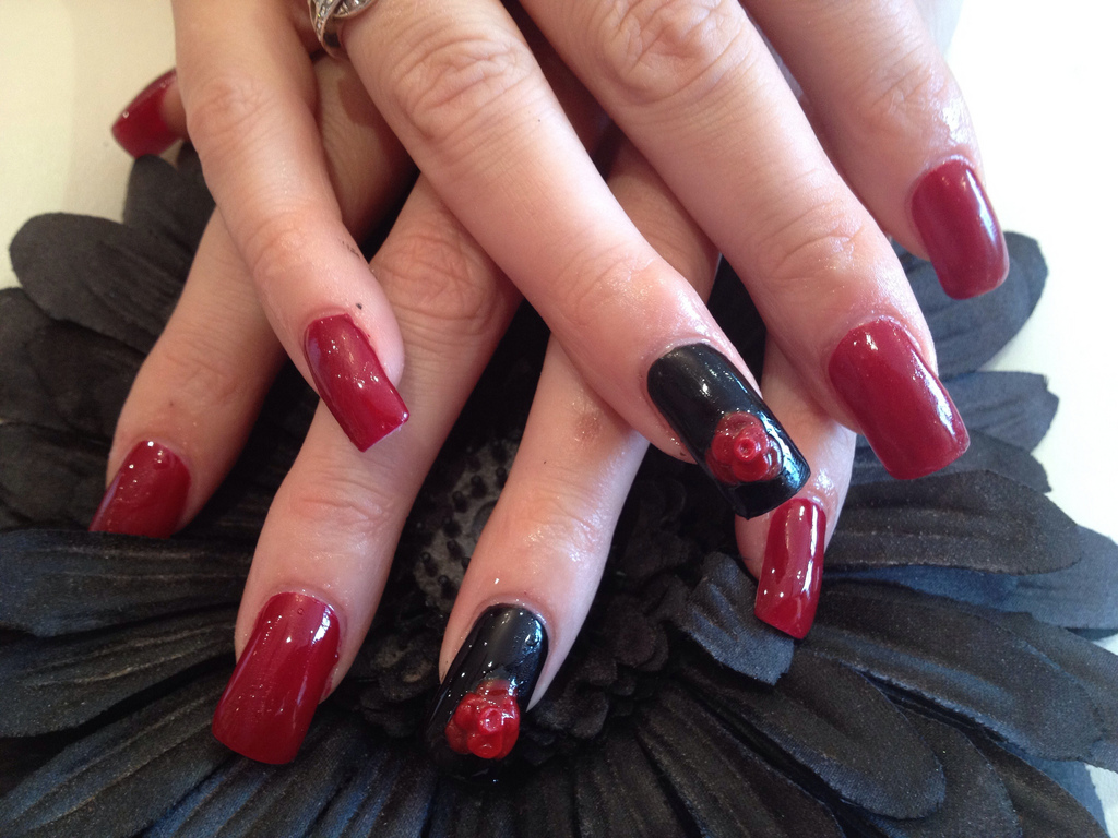 acrylic nails with red and black polish and 3d flower - nail