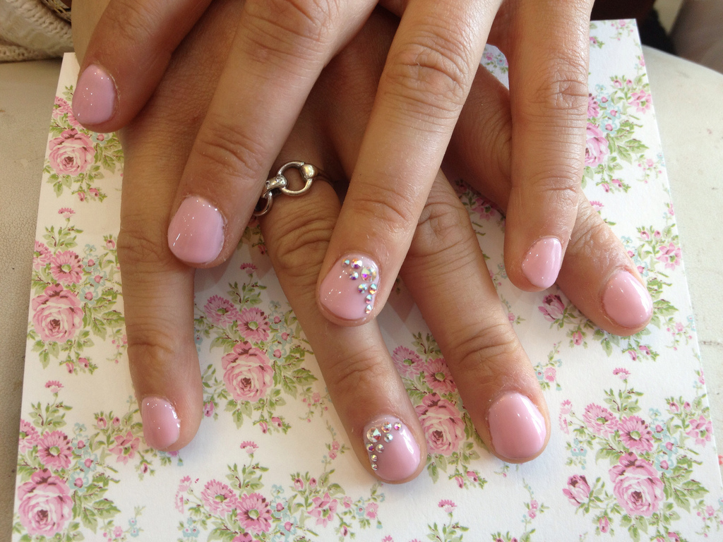 Pink gel on natural nails with Swarovski crystals on ring finger ...
