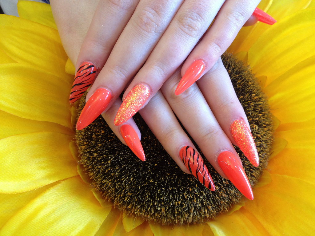 stiletto nails with orange gel polish and zebra print nail