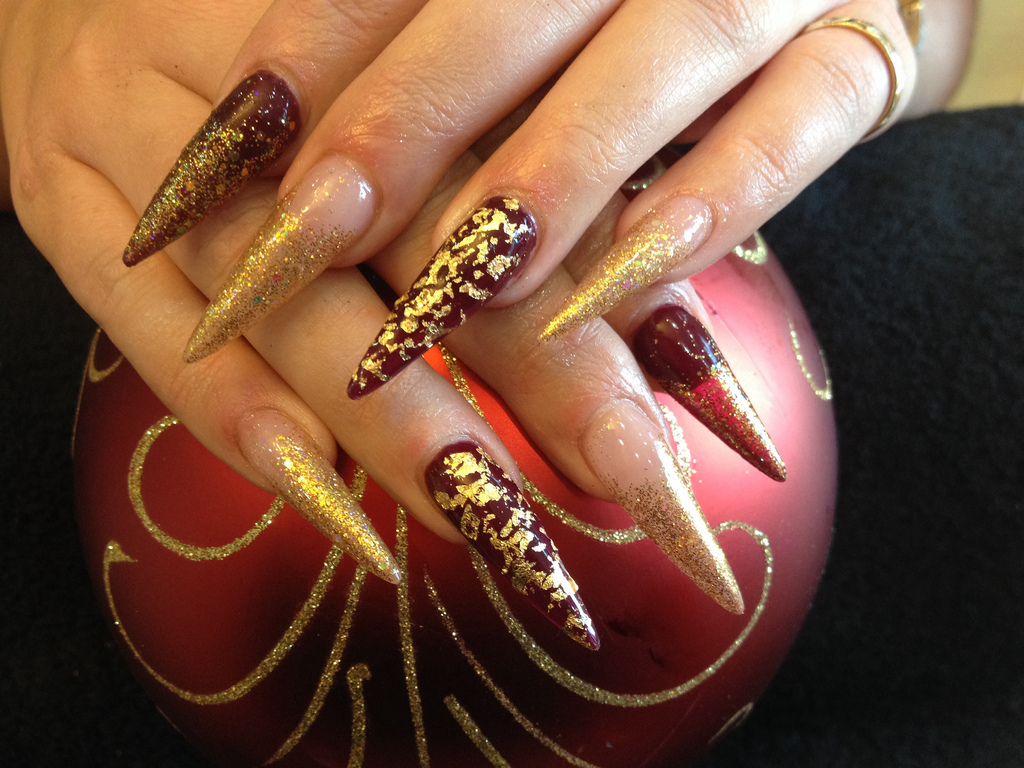 Stiletto nails with gold glitter and gold foil over deep red gel ...
