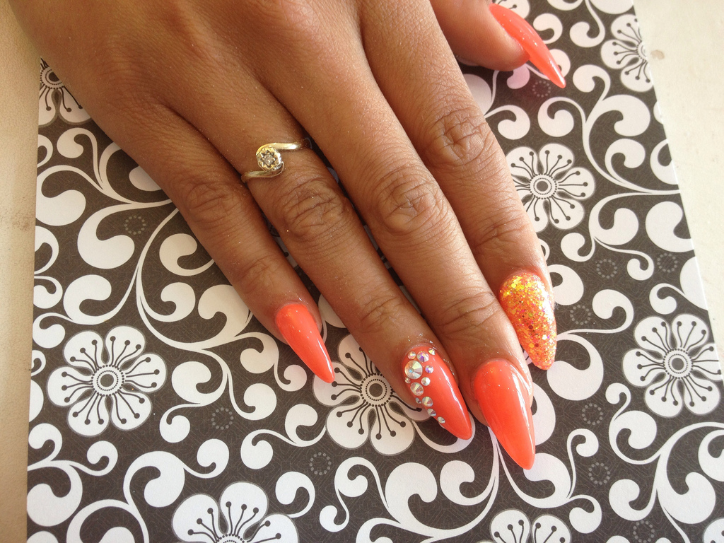 Stiletto nails with orange gel polish, glitter and Swarovski ...