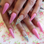 Stiletto Nails with Pink Gel Polish and Glitter on Ring Fingers