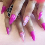 Stiletto nails with pink gel polish and glitter ring finger